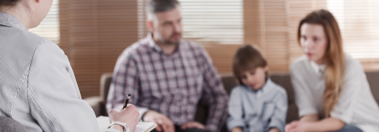 Rear view of female psychologist helping young family